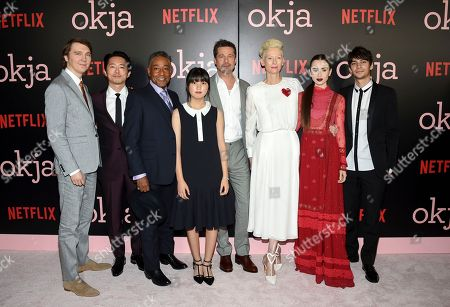 """Actors Paul Dano, left, Steven Yeun, Giancarlo Esposito, An Seo Hyun,Tilda Swinton, Lily Collins and Devon Bostick pose with executive producer Brad Pitt, center, at the premiere of Netflix's """"Okja"""" at AMC Loews Lincoln Square, in New York"""