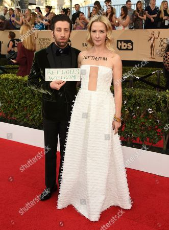 Simon Helberg, left, and Jocelyn Towne display protest signs against the U.S. policy of temporarily barring refugees and citizens of seven predominantly Muslim countries, at the 23rd annual Screen Actors Guild Awards at the Shrine Auditorium & Expo Hall, in Los Angeles