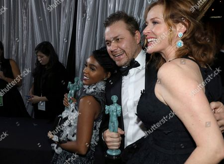 """Janelle Monae, from left, Theodore Melfi and Kimberly Quinn pose backstage as they pick up their awards for for outstanding performance by a cast in a motion picture for """"Hidden Figures"""" at the 23rd annual Screen Actors Guild Awards at the Shrine Auditorium & Expo Hall, in Los Angeles"""