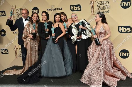 """Nick Sandow, from left, Elizabeth Rodriguez, Selenis Leyva, Diane Guerrero, Jackie Cruz, Lori Petty and Yael Stone pose in the press room with the awards for the award for outstanding performance by an ensemble in a comedy series for """"Orange Is The New Black"""" at the 23rd annual Screen Actors Guild Awards at the Shrine Auditorium & Expo Hall, in Los Angeles"""