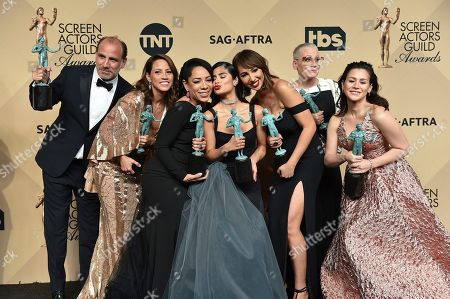 """Nick Sandow, from left, Elizabeth Rodriguez, Selenis Leyva, Diane Guerrero, Jackie Cruz, Lori Petty and Yael Stone pose in the press room with the award for outstanding performance by an ensemble in a comedy series for """"Orange Is The New Black"""" at the 23rd annual Screen Actors Guild Awards at the Shrine Auditorium & Expo Hall, in Los Angeles"""