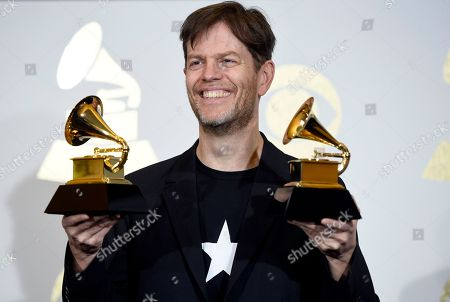 Donny McCaslin poses in the press room with the awards for at the 59th annual Grammy Awards at the Staples Center, in Los Angeles