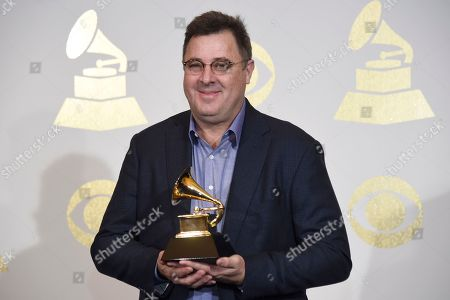 "Vince Gill, of The Time Jumpers, poses in the press room with the award for best American roots song for ""Kid Sister"" at the 59th annual Grammy Awards at the Staples Center, in Los Angeles"