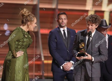"""Adele, left, and Greg Kurstin accept the award for record of the year for """"Hello"""" at the 59th annual Grammy Awards, in Los Angeles"""