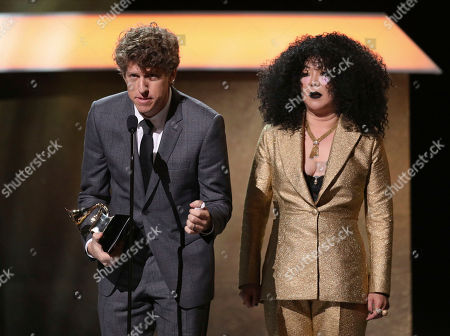 Greg Kurstin, left, accepts the award for producer of the year, non-classical as Margaret Cho looks on at the 59th annual Grammy Awards, in Los Angeles. Looking on from right is presenter Margaret Cho