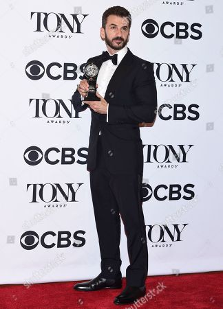 """Michael Aronov poses in the press room with the award for best performance by an actor in a featured role in a play for """"Oslo"""" at the 71st annual Tony Awards, in New York"""