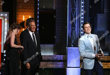 """Gavin Creel, right, accepts the award for best performance by an actor in a featured role in a musical for """"Hello, Dolly!"""" at the 71st annual Tony Awards, in New York. Looking on from left are presenters are Sutton Foster and Scott Bakula"""