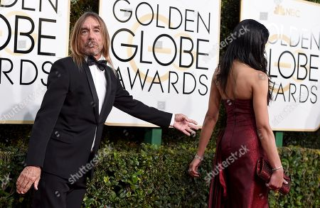 Iggy Pop, left, and Nina Alu arrive at the 74th annual Golden Globe Awards at the Beverly Hilton Hotel, in Beverly Hills, Calif