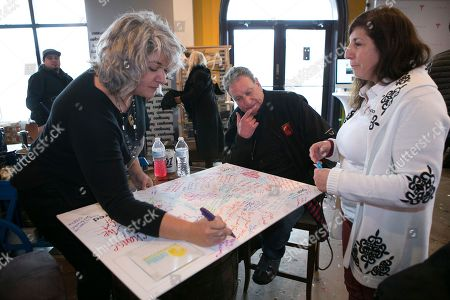 "Stock Picture of Trixie Garcia, the daughter of Grateful Dead guitarist Jerry Garcia, on hand for the premier of the Grateful Dead documentary ""Long Strange Trip,"" signs a poster for the non-profit Playing for Change Foundation the Music Lodge during the Sundance Film Festival, in Park City, Utah"