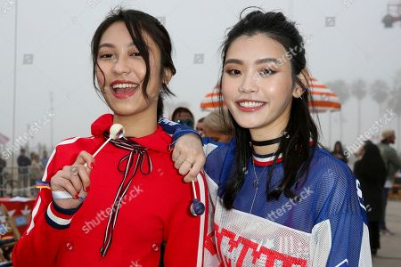 Anny Fan, left, and Ming Xi attend the Tommy Hilfiger TommyxGigi Runway Show at Venice Beach on in Los Angeles