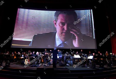 Conductor Mark Watters conducts the score from The Good Fight during WORDS + MUSIC, presented at the Television Academy's Wolf Theatre at the Saban Media Center in North Hollywood, Calif. Matthew Perry is pictured onscreen