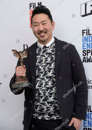 "Andrew Ahn poses with the John Cassavetes award for ""Spa Night"" in the press room at the Film Independent Spirit Awards, in Santa Monica, Calif"