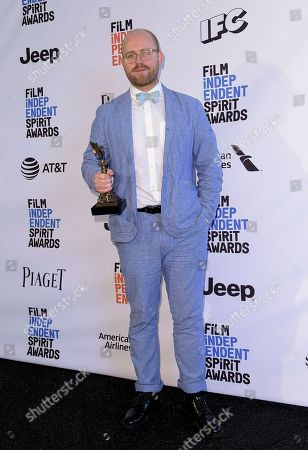 """James Laxton poses in the press room with the award for best cinematography for """"Moonlight"""" at the Film Independent Spirit Awards, in Santa Monica, Calif"""