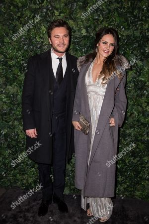 Ben Caring and Elle Caring pose for photographers upon arrival at the Charles Finch and Chanel pre Bafta party in London