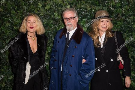 From left, a guest, Franc Roddam and Maryam D'Abo pose for photographers upon arrival at the Charles Finch and Chanel pre Bafta party in London