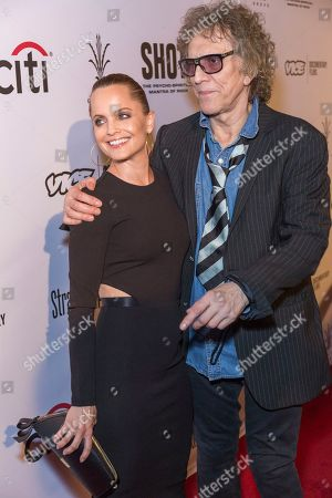 """Mena Suvari, left, and Mick Rock arrive at the LA Premiere of """"SHOT! The Psycho-Spiritual Mantra of Rock"""" at the Pacific Theatres at The Grove, in Los Angeles"""