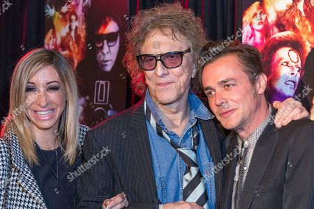 """Marisa Polvino, from left, Mick Rock, and Barnaby Clay arrive at the LA Premiere of """"SHOT! The Psycho-Spiritual Mantra of Rock"""" at the Pacific Theatres at The Grove, in Los Angeles"""