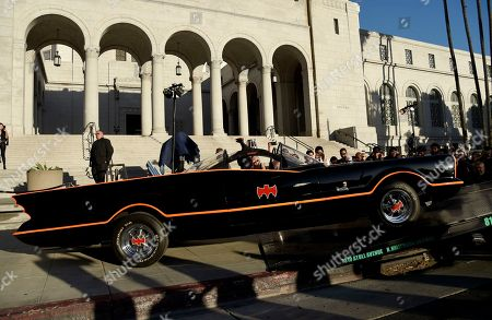 "A Batmobile gets loaded onto the sidewalk before a tribute to ""Batman"" star Adam West that includes lighting a Bat-signal at City Hall, in Los Angeles"