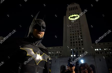 "Tony Bradshaw, of Los Angeles, dressed as Batman, poses in front of a Bat-Signal projected onto City Hall during a tribute to ""Batman"" star Adam West, in Los Angeles"