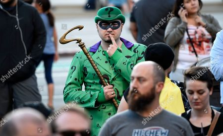 "Chat Evett, of La Junta, Colo., dressed as the Riddler, attends a tribute to ""Batman"" star Adam West that includes lighting a Bat-signal at City Hall, in Los Angeles"