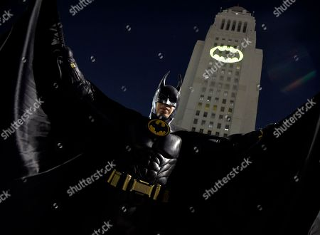 "A man poses in front of a Bat-Signal projected onto City Hall at a tribute to ""Batman"" star Adam West, in Los Angeles"