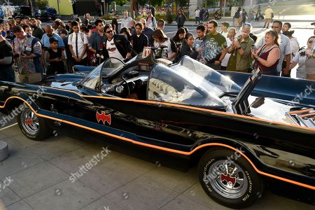 "Fans gather around a Batmobile before a tribute to ""Batman"" star Adam West that includes lighting a Bat-signal at City Hall, in Los Angeles"