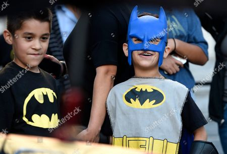 "Twin brothers Augustine Reynoso, left, and Vincent Reynoso, of Rancho Cucamonga, Calif., dress in Batman outfits at a tribute to ""Batman"" star Adam West that includes lighting a Bat-signal at City Hall, in Los Angeles"