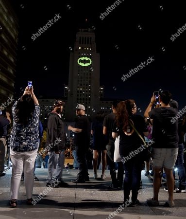 "Fans take photographs of a Bat-Signal projected onto City Hall following a tribute to ""Batman"" star Adam West, in Los Angeles"