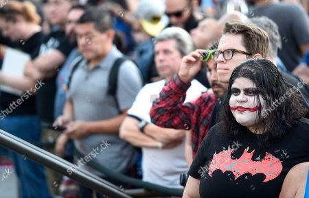 "Edith Recinos, of El Monte, Calif., right, dressed at the Joker, attends a tribute to ""Batman"" star Adam West that includes the lighting of a Bat-signal at City Hall, in Los Angeles"
