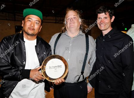 Chef Roy Choi, left and chef Daniel Patterson, right, receive the Los Angeles Times Restaurant of the Year award from writer Jonathan Gold at the Los Angeles Times Food Bowl launch party at Manuela and Hauser and Wirth, in Los Angeles