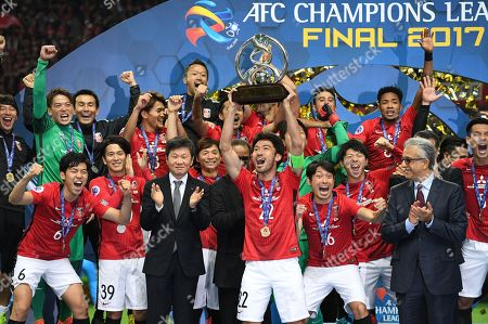 Yuki Abe of Urawa Reds holds up the trophy as he celebrates with his teammates after winning the AFC Champions League Final 2nd leg match