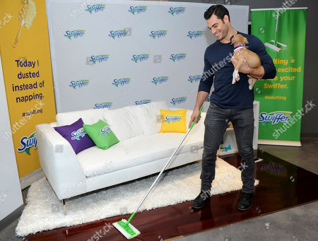 IMAGE DISTRIBUTED FOR SWIFFER - Pet Vet Dr. Evan Antin demonstrates one of the key adulting moments of new pet ownership - cleaning - while using a Swiffer Sweeper and holding an adoptable puppy from Bideawee Animal Shelter, in New York