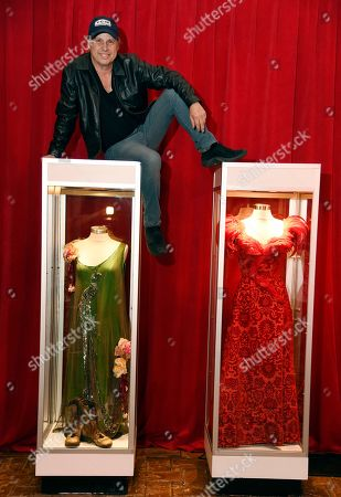 "Stock Photo of Todd Fisher, son of the late actress Debbie Reynolds, poses atop glass cases displaying two dresses that Reynolds wore in the 1964 film ""The Unsinkable Molly Brown,"" at the Hollywood Roosevelt Hotel, in Los Angeles"