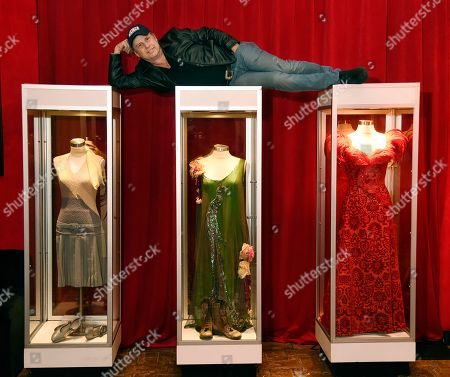 "Todd Fisher, son of the late actress Debbie Reynolds, poses atop glass cases displaying three dresses that Reynolds wore during her career, at the Hollywood Roosevelt Hotel, in Los Angeles. The dress on the left was featured in the 1952 film ""Singin' in the Rain"" while the dresses at center and right were worn by Reynolds in the 1964 film ""The Unsinkable Molly Brown"