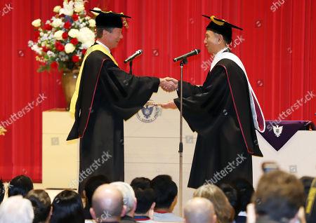 Grand Duke Henri of Luxembourg receives an honorary doctorate from Japan's Sophia University president Yoshiaki Terumichi (R) at Sophia University in Tokyo