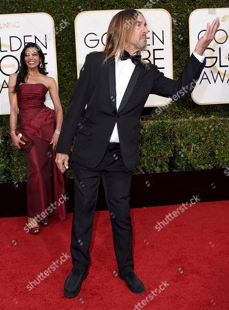 Nina Alu, background left, and Iggy Pop arrive at the 74th annual Golden Globe Awards at the Beverly Hilton Hotel, in Beverly Hills, Calif
