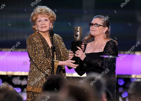 """Carrie Fisher, right, presents her mother Debbie Reynolds with the Screen Actors Guild life achievement award at the 21st annual Screen Actors Guild Awards at the Shrine Auditorium in Los Angeles. """"La La Land"""" star Ryan Gosling thanked Reynolds at the Palm Springs Film Festival, for serving as an inspiration to the cast and crew of the film"""
