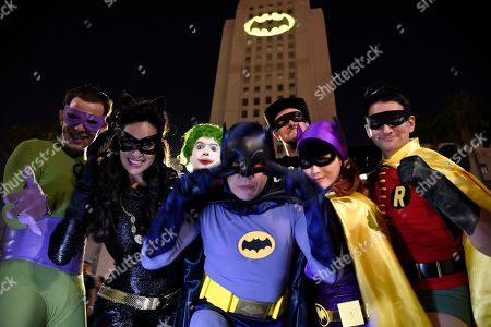 "Fans dressed as characters from ""Batman"" pose in front of a Bat-Signal projected onto City Hall following a tribute to ""Batman"" star Adam West, in Los Angeles"