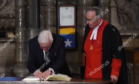 Germany's President Frank-Walter Steinmeier signs a visitors book next to The Very Reverend Dr John Hall (R), Dean of Westminster Abbey during a visit to the Anglican Westminster Abbey in London, Britain 28 November 2017. Frank-Walter Steinmeier and his wife are on a one day official visit to London.