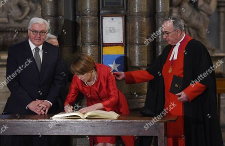 Germany's President Frank-Walter Steinmeier (R) and his wife Elke Budenbender (C) stand with The Very Reverend Dr John Hall (R), Dean of Westminster Abbey as they sign a visitor's book next the grave of the Unknown Warrior during a visit to the Anglican Westminster Abbey in London, Britain 28 November 2017. Frank-Walter Steinmeier and his wife are on a one day official visit to London.