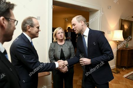 Prince William (R) shakes hands with Finnish businessman Jorma Ollila, former chairman and CEO of Nokia Corporation during a reception at the British Embassy in Helsinki