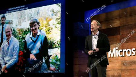 Stock Photo of Microsoft president Brad Smith shows a photo of company co-founders Steve Ballmer, left, and Bill Gates as he speaks at the annual Microsoft shareholders meeting, in Bellevue, Wash