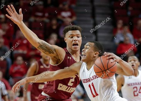 Stock Photo of Evan Taylor, Avery Wilson. Nebraska's Evan Taylor (11) loses his balance while trying to drive past Boston College's Avery Wilson (2) during the second half of an NCAA college basketball game in Lincoln, Neb., . Nebraska won 71-62