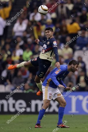 America's Carlos Vargas, left, heads the ball next to with Tigres' Andre Pierre Gignac during a Mexico soccer league semifinal first leg match at Estadio Azteca in Mexico City