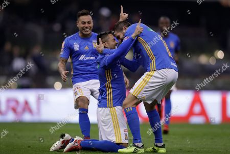 Tigres' Anselmo Juninho celebrates on his knees with teammate Andre Pierre Gignac as Silvio Romero runs up to them, after scoring a penalty kick against America during a Mexico soccer league semifinal first leg match at Estadio Azteca in Mexico City