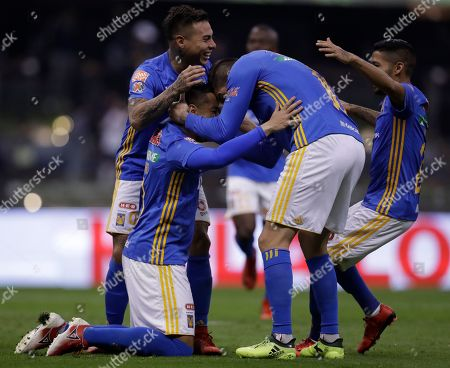 Tigres' Anselmo Juninho celebrates on his knees with teammate Andre Pierre Gignac, second from right, and Silvio Romero, left, after scoring a penalty kick against America during a Mexico soccer league semifinal first leg match at Estadio Azteca in Mexico City