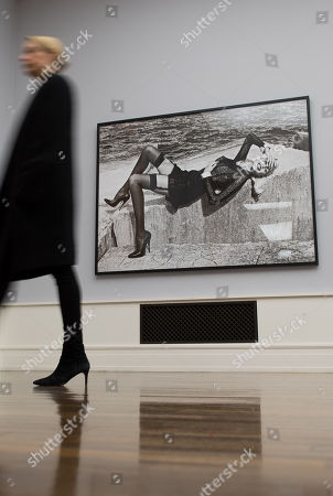 Stock Image of A woman passes a photo with German model Nadja Auermann by German-Australian photographer Helmut Newton in the 'A Gun for Hire' display at the Helmut Newton Stiftung museum for photography in Berlin, Germany, 30 November 2017. The exhibition 'Guy Bourdin. Image Maker / Helmut Newton. A Gun for Hire / Angelo Marino. Another Story' presents more than 200 pictures by the three photographers from 01 Dezember on.