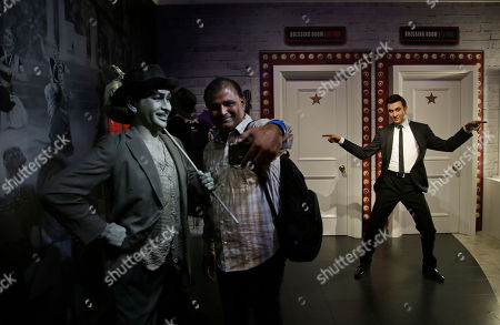 A visitor takes a selfie with a wax figure of Bollywood actor Raj Kapoor, left, as the wax figure of Bollywood actor Ranbir Kapoor is seen in the background during a press preview of Madame Tussauds Wax Museum in New Delhi, India, . New Delhi's Madam Tussauds museum has become the 23rd Madam Tussauds museum worldwide and will house wax statues of Indian and international icons
