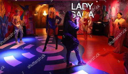 An Indian visitor takes pictures next to wax figures of Canadian singer Justin Bieber (L), US singers Beyonce Knowles (2-L) and Lady Gaga (2-R), and Indian singer Asha Bhosle at the Madame Tussauds wax museum in New Delhi, India, 30 November 2017. The wax museum will be open for the visitors from 01 December on. Madame Tussauds New Delhi features 50 wax figures of personalities from the fields of sports, music, film, history and politics.