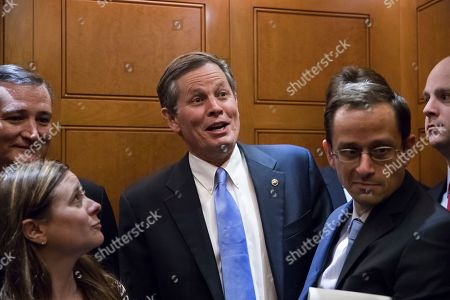 Pausing for a reporter's question, Sen. Steve Daines, R-Mont., and other senators squeeze into an elevator as they rush to the chamber to vote on amendments as the Republican leadership works to craft their sweeping tax bill, on Capitol Hill in Washington, . It would mark the first time in 31 years that Congress has overhauled the tax code, making it the biggest legislative achievement of President Donald Trump's first year in office